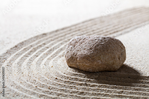 zen sand still-life - textured stone on sinuous waves for concept of serenity or beauty spa with inner peace, closeup
