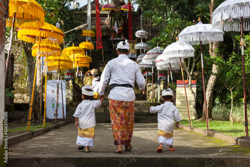 In de dag Bali Man with children walks up the stairs during the celebration before Nyepi (Balinese Day of Silence). Ubud, Indonesia.