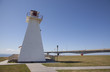 lighthouse with confederation bridge in background on prince edw