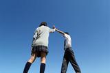 青空の下ハイタッチをする高校生男女