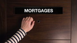 Mortgages concept, female hand knocking on bank office door, mortgage department
