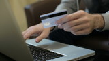 Man paying bill, shopping online, inserting credit card number. A man paying for online shopping using laptop and credit card. close up