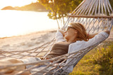 beautiful girl in a hammock on the beach, watching the sunset