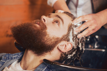 professional barber washing head of his client