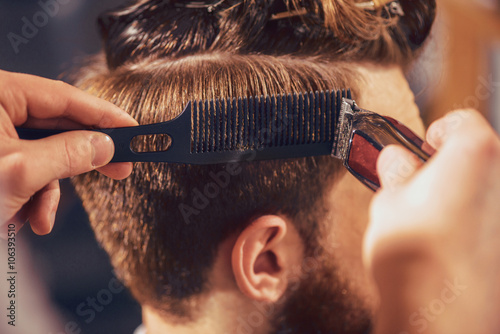 Professional barber cutting hair of his client Poster