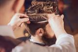 Profesjonalny fryzjer stylizujący włosy swojego klienta