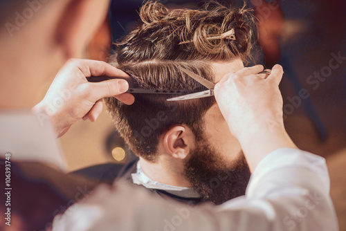 Fototapeta Professional barber styling hair of his client