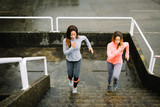 Urban fitness women running and climbing stairs for legs power and strength training. Female athletes working out outdoor in rainy winter day.