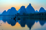 Silhouette of Fisherman with Cormorant Bird on Boat China River
