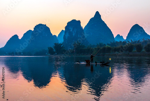 Fotobehang Guilin Silhouette of Fisherman with Cormorant Bird on Boat China River