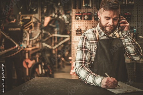 Foto op Canvas Pizzeria Stylish bicycle mechanic takes order by phone in his workshop.