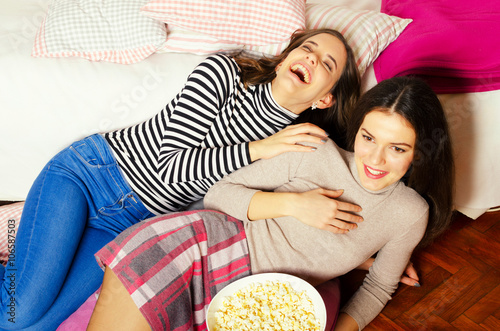 Plagát Two beautiful teenage girls eating popcorn and watching movies