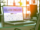 Fototapety Learn English Concept. Closeup Landing Page on Laptop Screen in Doodle Design Style. On Background of Comfortable Working Place in Modern Office. Blurred, Toned Image. 3D Render.