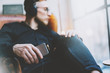 Photo handsome bearded man headphones listening to music modern loft studio.Man sitting in vintage chair looking window,holding smartphone and relaxing.Blurred background.Horizontal, film effect.