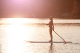 silhouette of young girl paddle boarding at sunset01