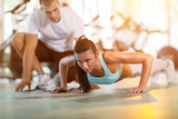 woman doing push ups under supervision of a trainer
