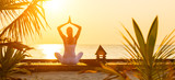 Fototapety Young woman practicing yoga on the beach at sunset
