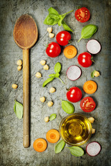 Wooden spoon and fresh ingredients on old background