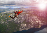 Young man jumping from a cliff into the abyss.