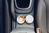 Fototapety Coffee cups inside car holder between seats