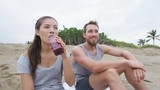 Couple sharing beet juice on beach after exercise relaxing after workout running outdoor. Mixed race couple smiling happy together sitting relaxed enjoying healthy active living. RED EPIC SLOW MOTION.