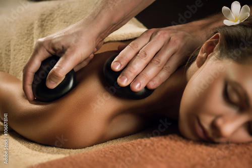 Beautiful girl has stone massage.