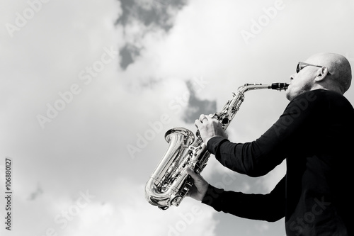 Saxophonist playing on saxophone on blue sky background Poster