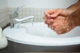 Man washing hands in washbasin