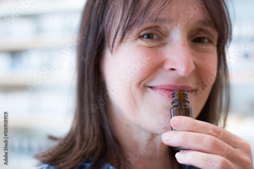 Poster, Tablou Frau schnuppert an duftender Flasche