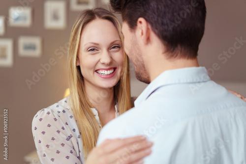 Poster lachende frau umarmt ihren mann