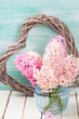 Fresh pink hyacinths in vase  and decorative heart on white wood