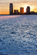 Winter view of the Frozen Hudson River and ice at sunset with skyline of Jersey City skyscrapers
