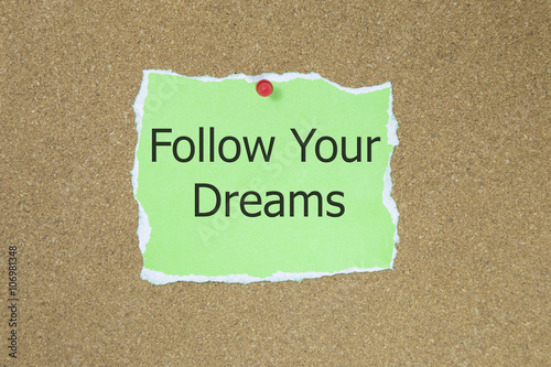 The phrase follow your dreams in text on a green sticky note posted to a cork notice board Poster