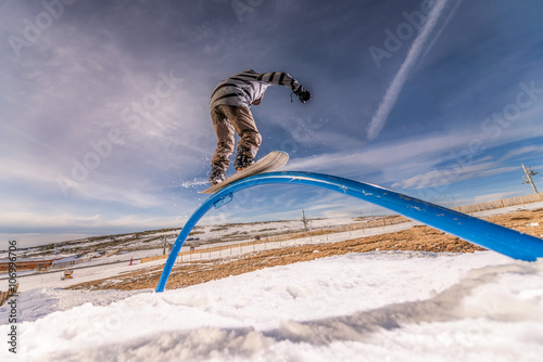 Snowboarder sliding on a rail Poster