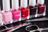 Nail polishes in a row and manicure set on black background.