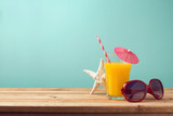 Summer holiday vacation concept with orange juice and sunglasses on wooden table