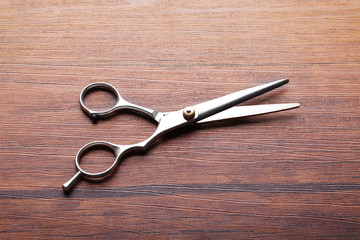 Professional metal scissors lying on the wooden table, close up