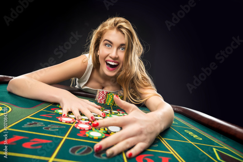 Young pretty women playing roulette wins at the casino плакат