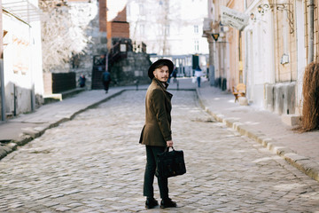 handsome young bearded hipster man guy in hat Fedora on street with suitcase. Retro vintage fashion look