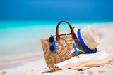 Fototapety Beach consept - straw bag, hat, sunglasses and towel on white beach