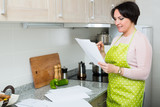 Happy housewife reading insurance contract