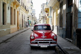 street scene in havana, cuba with old car