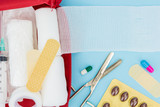 Opened first aid kit with medical equipment, on light blue background