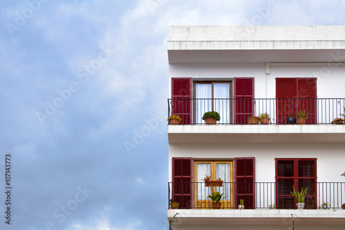 Classic latino spanish building facade with terrace and coloured windows with shutters
