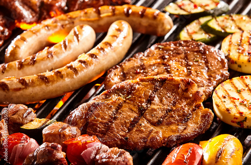 Fototapeta Various meats and vegetables on hot grill
