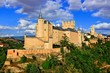 Beautiful Segovia Castle, Spain perched on a rocky hill with the old town behind