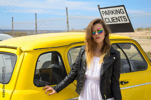 Young Hippie girl standing next to an old vintage retro car