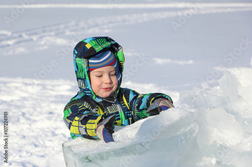 The little boy in a color jacket with a hood the piece of ice holding in hand