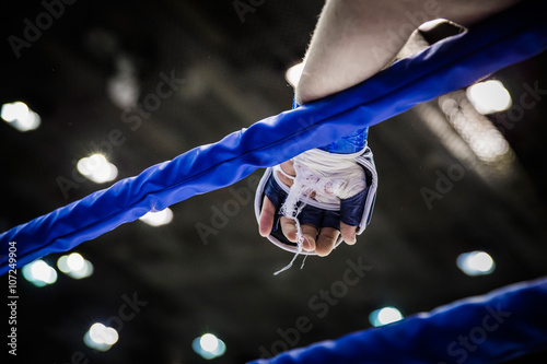 hand of fighter on ropes of ring during competition in mixed martial arts