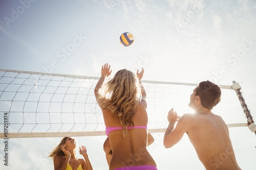 Poster Friends playing beach volleyball
